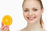 Smiling woman presenting an orange slice