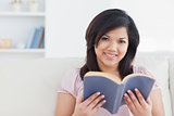 Woman sitting on a couch while holding a book