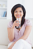 Woman smiling while sitting on a couch and holding a glass of wa