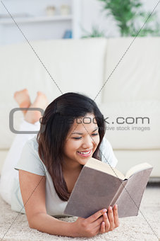 Woman lays on the floor as she reads a book