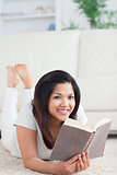 Smiling woman lying on the floor while reader a book