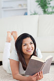 Woman smiling and holding a book as she lays on the floor