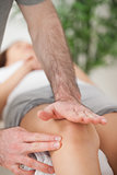 Physiotherapist using his hand palm to massage a knee