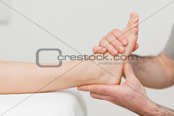 Hands of an osteopath massaging a foot