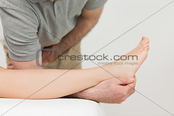 Serious physiotherapist working on an ankle