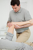 Serious physiotherapist looking at the knee of a patient