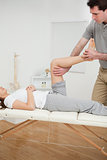 Serious osteopath bending the leg of a woman