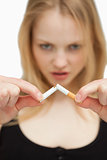 Young woman breaking a cigarette