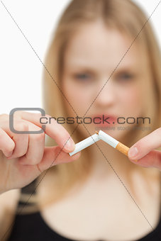 Close up of a blonde-haired woman breaking a cigarette