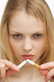 Close up of a serious woman breaking a cigarette