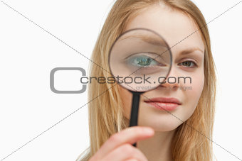 Close up of a woman placing a magnifying glass on her eyes
