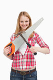Smiling woman holding a saw and a hammer