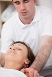 Physiotherapist manipulating the neck of his patient