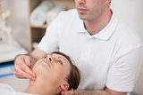 Physiotherapist pressing two fingers on the neck of his patient