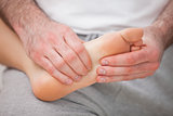 Podiatrist massaging the foot of a woman while holding it on his