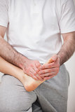 Podiatrist manipulating the foot of a woman while holding it on