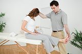 Physiotherapist manipulating his patient while standing