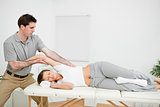 Chiropractor stretching the arm of his patient while holding it