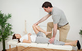 Woman being examining her leg by a chiropractor