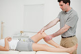 Physiotherapist examining the knee of his patient while touching