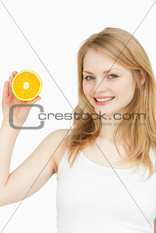 Smiling woman presenting an orange
