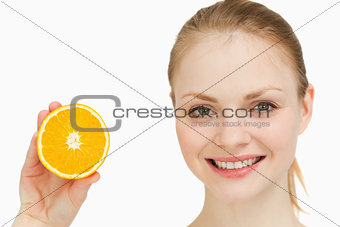 Close up of a cheerful woman presenting an orange