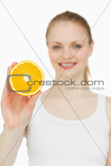 Blonde-haired woman holding an orange