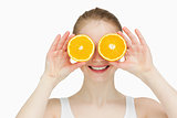 Smiling woman placing oranges on her eyes