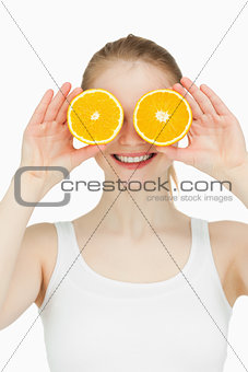 Cheerful woman placing oranges on her eyes