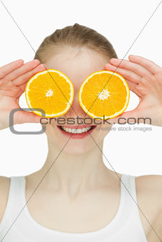 Close up of a woman placing oranges on her eyes