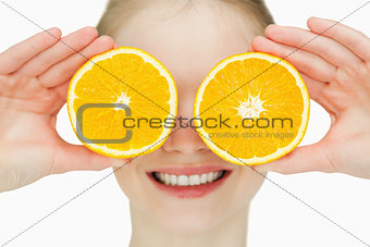 Close up of a cheerful woman placing oranges on her eyes