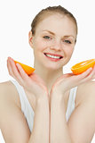 Close up of a smiling woman holding oranges