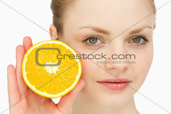 Close up of a woman presenting an orange