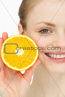 Close up of a smiling woman holding an orange