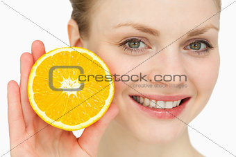 Blond-haired woman presenting an orange
