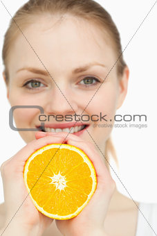 Close up of a woman squeezing an orange between her hands