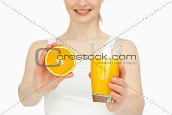 Woman presenting an orange while holding a glass