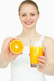 Smiling woman presenting an orange while holding a glass