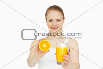 Cheerful woman presenting an orange while holding a glass