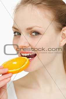 Close up of a woman placing an orange slice in her mouth