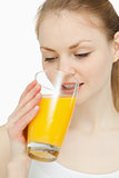 Woman drinking a glass of orange juice while looking at it