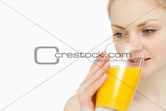 Woman drinking a glass of orange juice while looking away