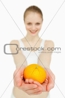 Close up of a woman presenting a tangerine