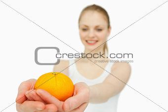 Cheerful woman presenting a tangerine