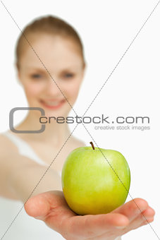 Close up of a woman presenting an apple