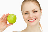Blonde-haired girl smiling while holding an apple