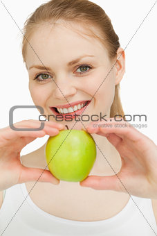 Blonde-haired girl smiling while presenting an apple