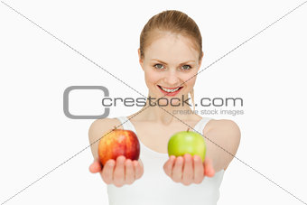 Smiling woman presenting two apples