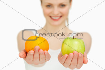 Young woman presenting fruits while smiling