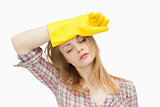 Woman wearing cleaning gloves while wiping her brow